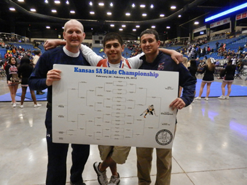 BRYANT GUILLEN stands with Coach Patrick Kelly and Assistant Coach Flores after placing first at State.  Guillen earned a 4-0 record and a state title in the 160 lb. weight class.  (Photo by Heather Guillen-Woltje)