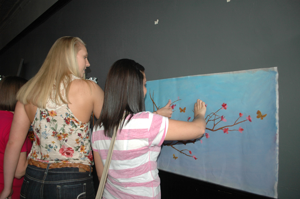 Seaman grads and former basketball team members Kara Lee and Kylie Shugart leave their fingerprints on a painting designed by art teacher Stephanie Munoz-O'Neil.  Earlier in the day, current members of the basketball left their prints on the painting in memory of their coach.