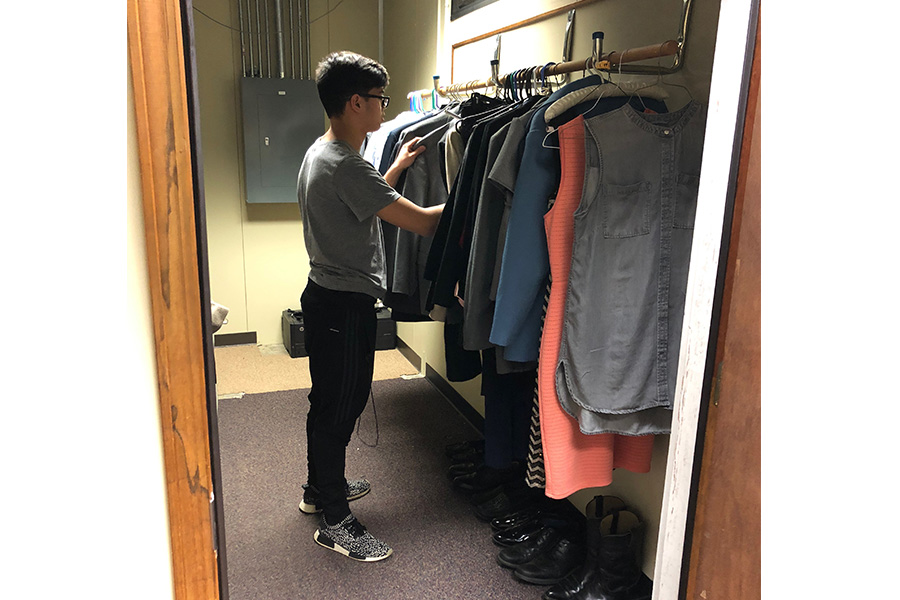 Junior Nathan Soriano searches through the new career closet for an outfit for his upcoming interview. (Photo by Jacob Wildeman)