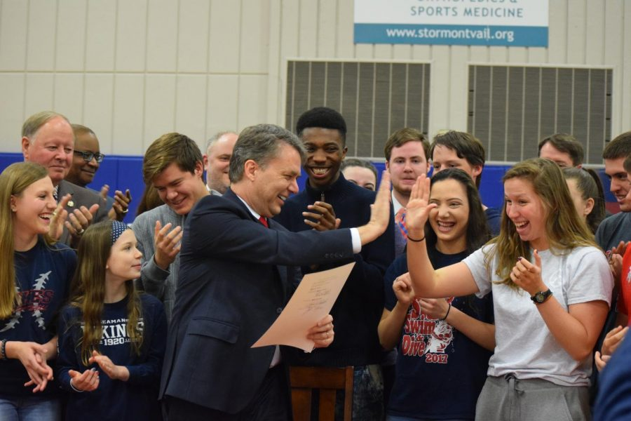 BIG MOMENT:  Governor Jeff Colyer gives a high five to senior Mackenzie Moylan right after signing the bill.  The school received a commemorative copy of the bill to display.  (Photo by Regan Bond)