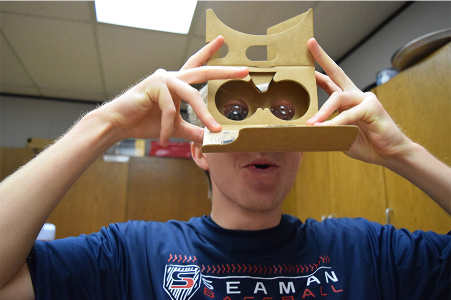 Senior Laine Marston tries on the new virtual reality glasses in the library.  They are a Google product and work with Google Expedition.  (Photo by Ruth Requejo)