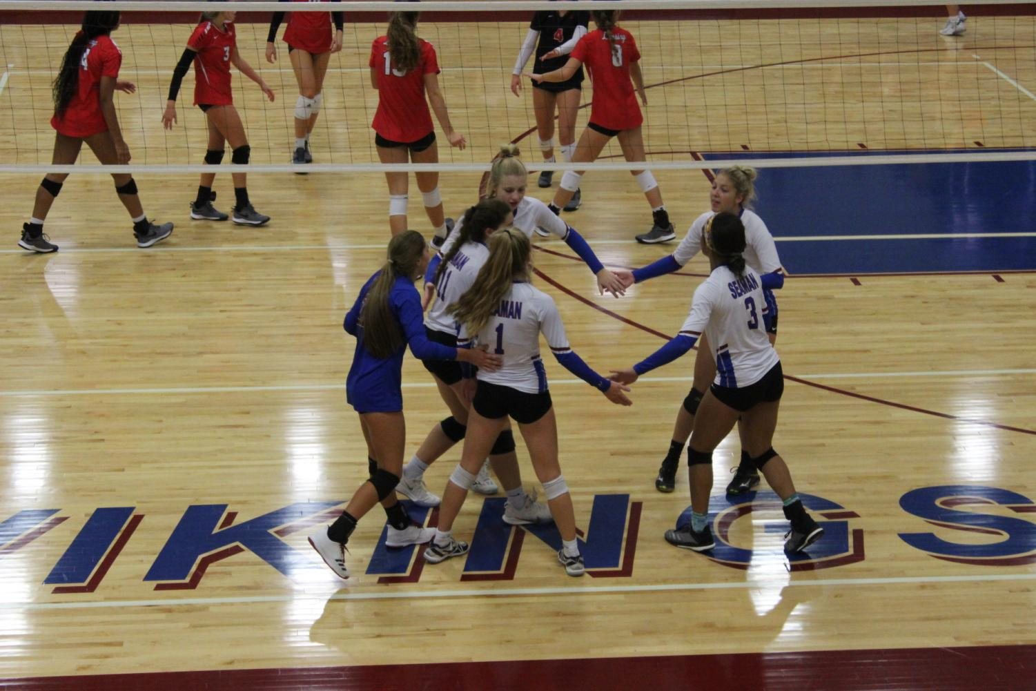 Varsity starters celebrate a kill at their home tournament in a match against Lansing. The Lady Vikes ended the tournament in second place.