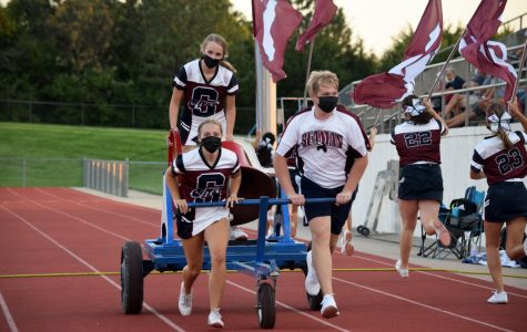 Seniors and Hannah Watkins, Isabel Freisberg Tyler Parkhurst run the bell at the scrimmage on August 28.  The cheerleaders wore their masks and practiced social distancing throughout the game.
