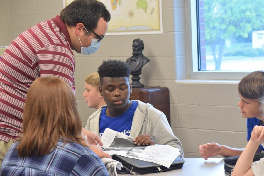 Mr.Hecker helps a student in his history class.