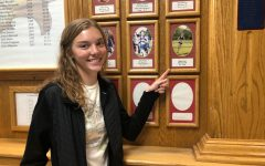 Bethany Druse poses next to a picture of the record she broke this year. Druses name is posted three times in the SHS Cross Country Hall of Fame.